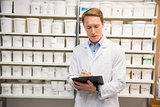 Handsome pharmacist writing on clipboard