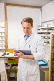 Focused pharmacist using tablet pc