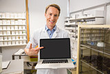 Happy pharmacist showing laptop screen