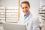 Happy pharmacist using his laptop