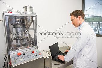 Focused pharmacist using his laptop