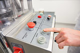 Pharmacist pressing button on machine
