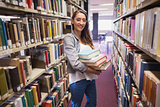 Pretty student smiling at camera in library
