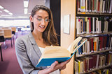 Pretty student reading book in library