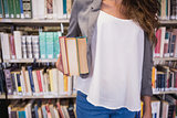 Pretty student holding books in library