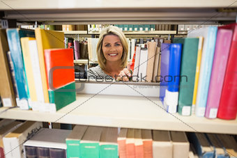Mature student taking a book in library