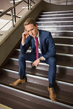 Stressed businessman sitting on steps