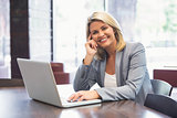 Blonde businesswoman smiling using laptop