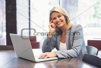 Blonde businesswoman smiling using laptop
