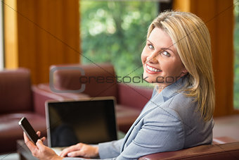 Blonde businesswoman using her phone