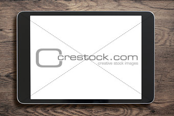 Black tablet pc on old wood background