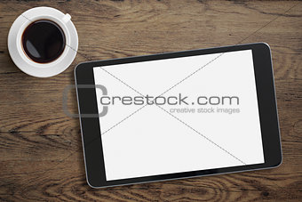 Black tablet pc on table desk with coffee cup