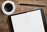 Tablet pc on table desk with coffee cup and pencil