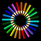 Color pencils in arrange in color wheel colors on black backgrou