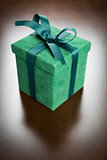Green Gift Box with Ribbon and Bow Resting on Wood