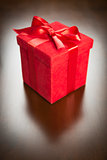 Red Gift Box with Ribbon and Bow Resting on Wood