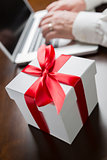 White Gift Box with Red Bow Near Man using Laptop