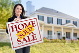 Woman Holding Sold Home Sale Sign in Front of House