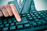 businessman pressing the intro key of a computer keyboard