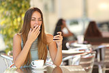 Woman yawning while is working at breakfast in a restaurant