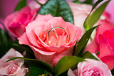 Two wedding rings on rose in bridal bouquet