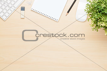 Office table with notepad, computer and flower