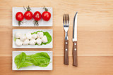 Tomatoes, mozzarella, green salad leaves and silverware