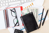 Office desk with reports, blank notepad and money cash
