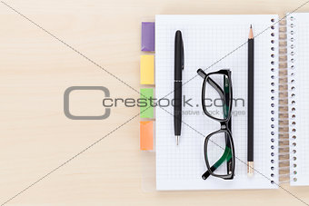 Office table with glasses over notepad, pen and pencil