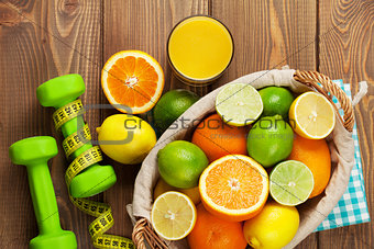 Citrus fruits in basket and dumbells. Oranges, limes and lemons