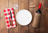 Table setting with empty plate, wine glass and red wine bottle