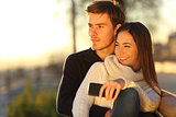 Couple relaxing and hugging looking at sunset