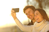 Couple taking selfie photo with a smart phone at sunset