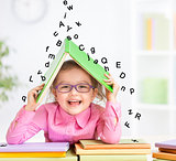 Smart smiling kid in glasses taking refuge under book roof from falling letters