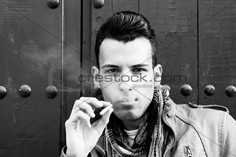 Attractive young man smoking cigarette