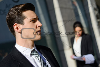 Attractive young businessmam and businesswoman in urban backgrou