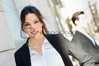 Attractive businesswoman standing outside of company building. C