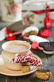 Cup of cocoa and gingerbread heart on wooden table.