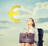 Businesswoman sitting on office chair, looking at euro sign in the air