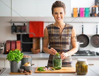 Portrait of happy young housewife pickling cucumbers in kitchen