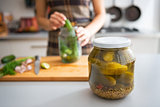 Closeup on jar of marinated cucumbers on table and housewife pic