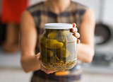 Closeup on young housewife showing jar of pickled cucumbers