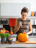 Young housewife pumpkin in kitchen