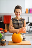 Portrait of happy young housewife with pumpkin in kitchen