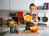 Portrait of happy young housewife in kitchen showing pumpkin