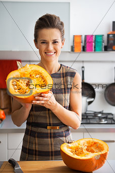 Portrait of happy young housewife showing half of pumpkin