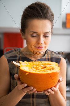 Portrait of happy young housewife enjoying fresh pumpkin