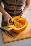 Closeup on young housewife removing filling from pumpkin