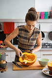 Young housewife removing filling from pumpkin