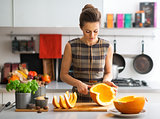 Young housewife cutting pumpkin in kitchen